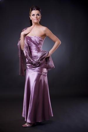 stole: Beautiful young woman posing, wearing a light purple evening dress with stole. Stock Photo