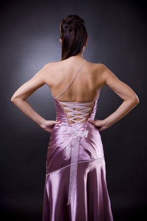 Back of a young woman wearing light purple laced evening dress, standing with arms on hip. photo