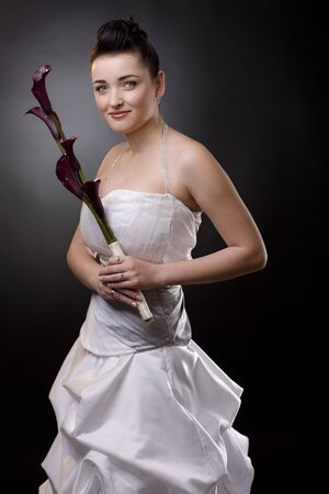Studio portrait of a happy young bride posing in a white wedding dress, holding purple flowers, smiling. photo