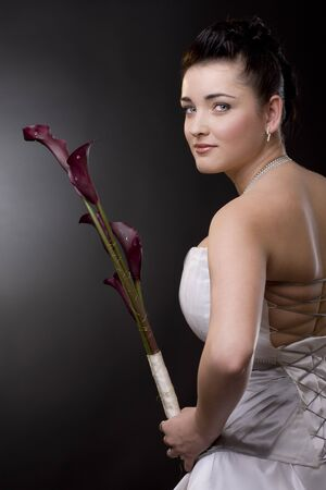 Studio portrait of a young bride posing in a white wedding dress, holding purple flowers, looking back. photo