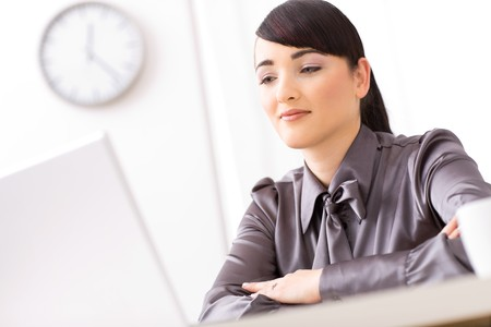 Young businesswoman sitting arms crossed at her desk, reading a document on her laptop. photo