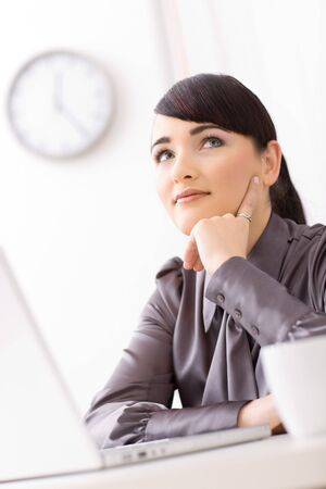Young businesswoman daydreaming in her office leaning on her hand, looking up. Stock Photo - 4204790