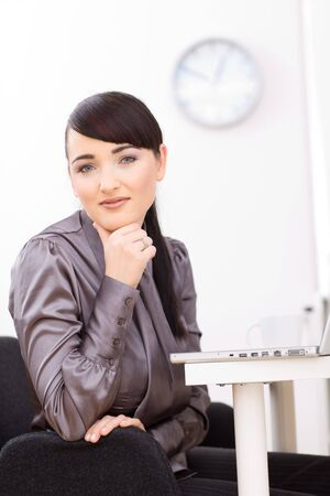 Young businesswoman thinking at her desk in the office, leaning on her hand. Stock Photo - 4204801