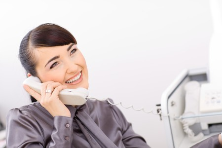 Happy businesswoman talking on landline phone in the office. photo