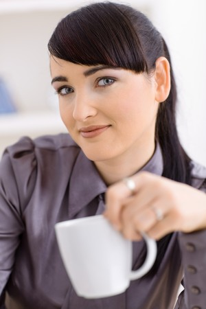 Colseup portrait of happy young women drinking coffe, smiling and looking at camera. photo