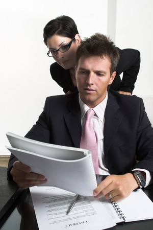 Young businessman and his assistant are looking-over business documents. Stock Photo - 4209056