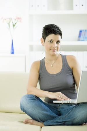 outworking: Young woman sitting on sofa at home working on laptop computer. Stock Photo