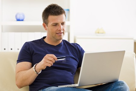 Man shopping online from home using credit card and laptop. Stock Photo - 4209119