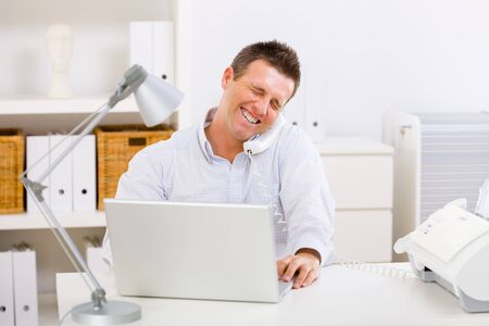 Business man working on computer at home calling on phone. Stock Photo - 4209113