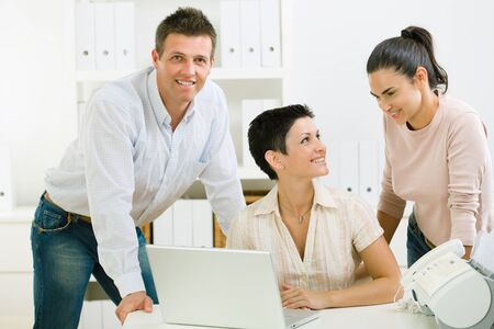 Team of happy office people working on laptop computer.  photo