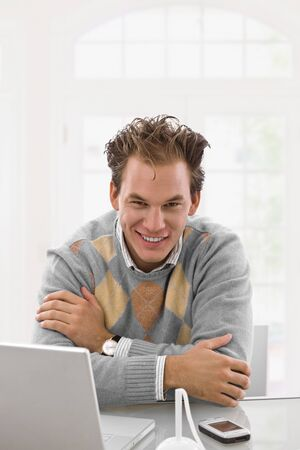 Happy young man working on laptop computer at home, smiling. Stock Photo - 4209122