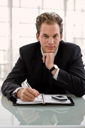 Businessman sitting at desk, planning timetable in notebook. photo