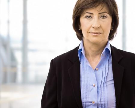 only senior women: Portrait of senior businesswoman at office lobby.