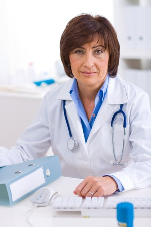 Senior female doctor sitting at desk working at offiice. Stock Photo - 4209102