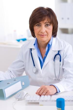 doctora: Superior femenino m�dico sentado en mesa de trabajo en offiice.