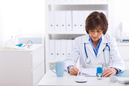 image consultant: Senior female doctor sitting at desk working at offiice. Stock Photo