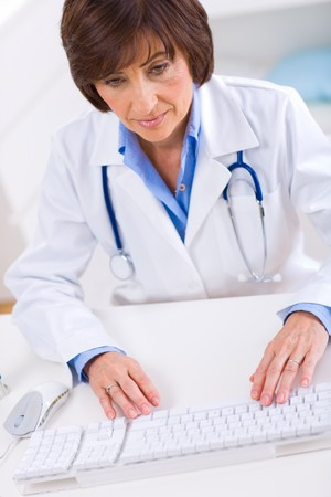 Senior female doctor working on computer at offiice. photo