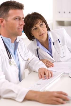 의료 의사가 사무실에서 일하는 데스크 앉아입니다.