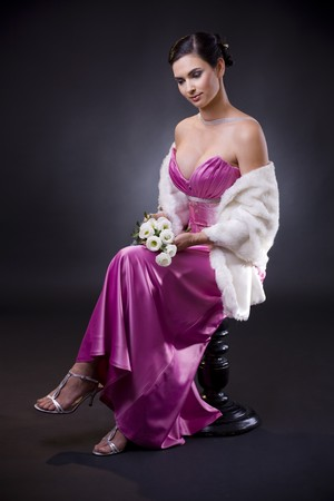 Beautiful young woman sitting on a chair wearing purple evening dress with white fur stole, holding bouqet of white roses. Stock Photo