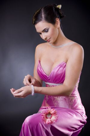 Beautiful young woman sitting on a chair wearing purple evening dress adjusting her bracelet. photo