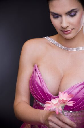 Beautiful young woman wearing purple evening dress daydreaming, looking a flower in her hand. photo
