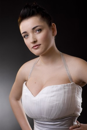 Portrait of a beautiful young bride wearing white wedding dress, looking at camera. photo