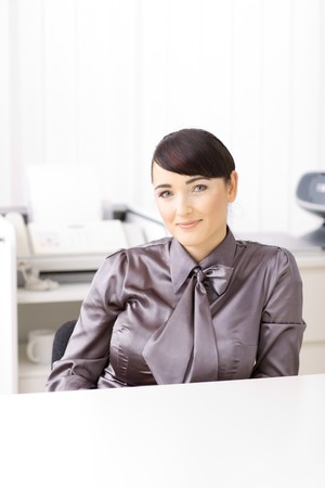brigt: Portrait of a smiling businesswomen in a brigt office, looking at the camera. Stock Photo