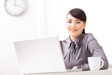 Happy young businesswoman working on her laptop, smiling and looking at camera in a bright office. photo