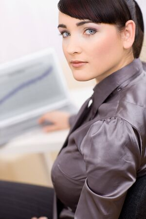 Young businesswoman working at her desk and looking seriously at camera. photo
