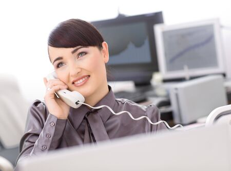Young female customer service operator talking on landline phone, smiling. Stock Photo - 4209095