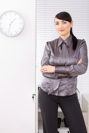Casual youg businesswomen standing arms crossed in office, smiling and looking at camera. photo