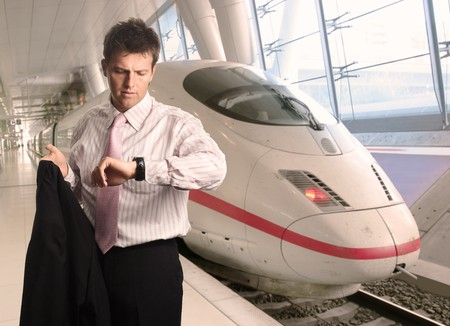Businessman is looking at his watch on a futuristic railway station. Stock Photo - 4209097