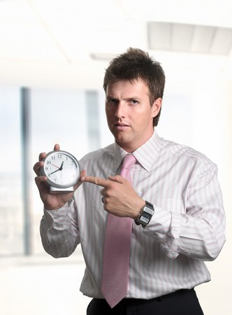 Conceptual image about the importance of time in the business. Businessman shows the time on a clock and he looks a bit angry. Stock Photo - 4209108