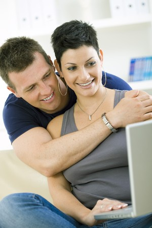 Happy young couple browsing internet on laptop computer at home, smiling. Stock Photo - 4239988