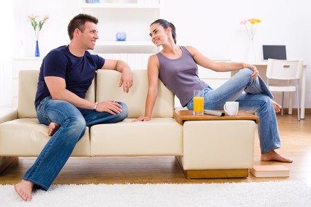 Happy young couple sitting on sofa at home, smiling. Stock Photo - 4239983