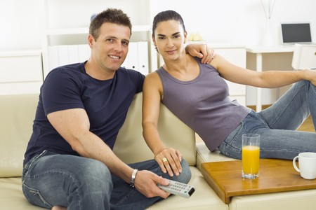 Happy young couple sitting on sofa at home, watching TV. photo