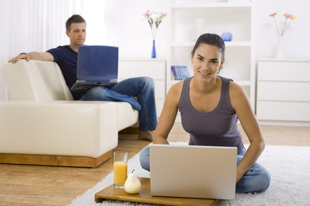 Young woman sitting on floor at home using laptop computer, smiling. photo