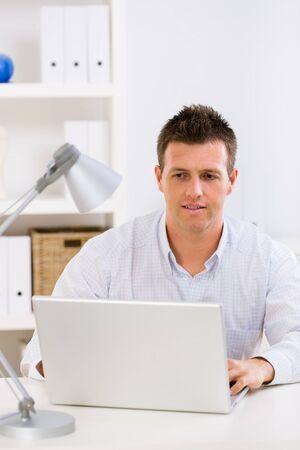 outwork: Hombre de negocios trabajando en ordenador port�til en casa. Foto de archivo