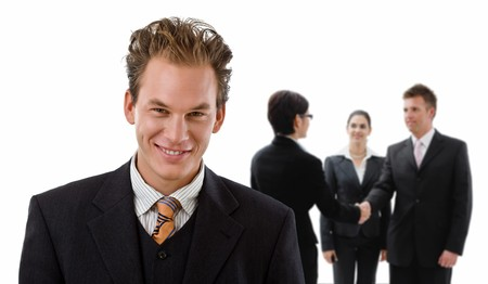 Team of business people, businessman in front, handsake in background. Stock Photo - 4239939