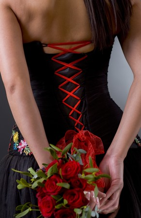 Laced back side of a black cocktail dress, bouqet of red roses. photo
