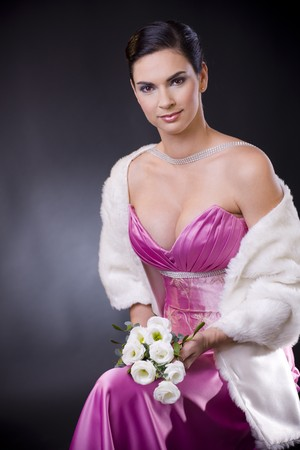 Beautiful young woman sitting on a chair wearing purple evening dress with white fur stole, holding bouqet of white roses. photo
