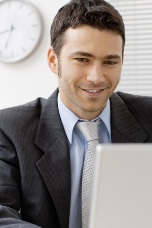 Portrait of happy smiling young businessman at office. Stock Photo - 4239985