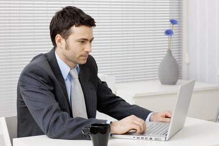 Young businessman working on laptop computer at office. photo