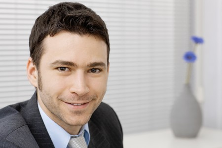 Portrait of happy smiling young businessman at office. Stock Photo - 4240494