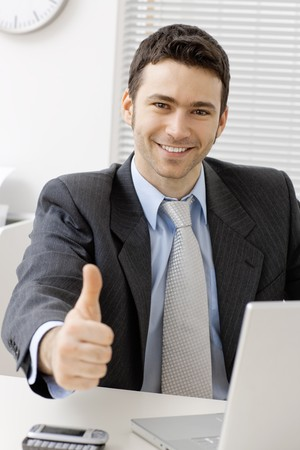 Happy young businessman showing success with thumb up at office, smiling. Stock Photo