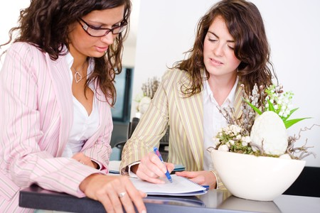 reviewing: Casual businesswomen working together in team at office reception, looking at documents, talking. Stock Photo