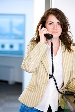 Young female receptionist receiving phone calls at office reception, smiling. photo