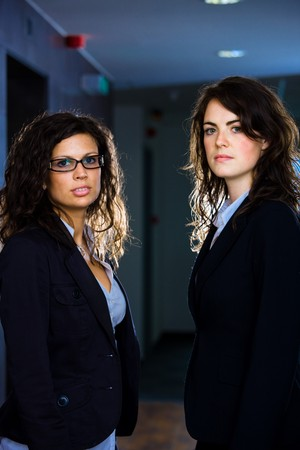 Portrait of two young businesswomen standing at office corridor, looking at camera. photo