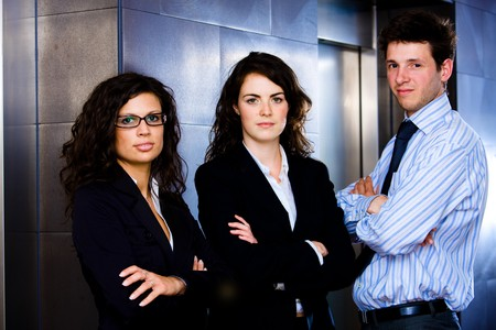 Portrait of successful happy business team posing at office lobby in front of elevator. Dark background. Stock Photo - 4244983