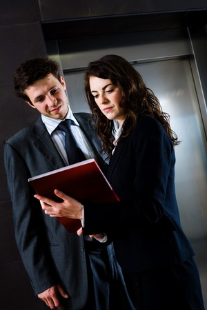 corporate image: Young businesspeople working together at office corridor, looking at red document folder, reading reports.